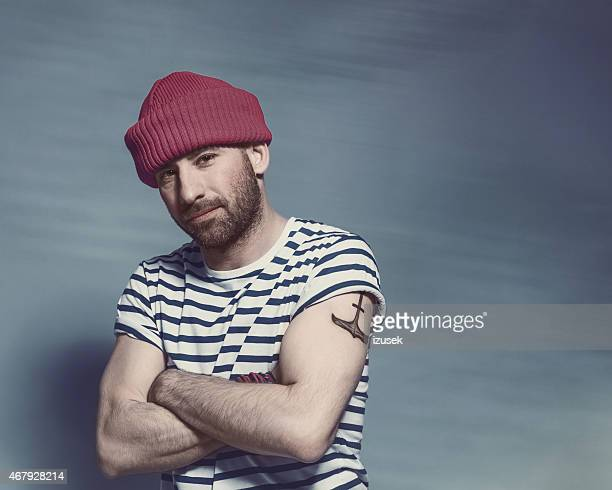 Bearded sailor man wearing striped t-shirt and wool cap