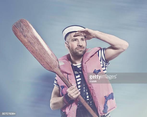 Bearded sailor wearing life jacket holding paddle
