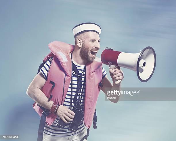 Bärtiger Seemann mit Schwimmweste schreien auf Megafon