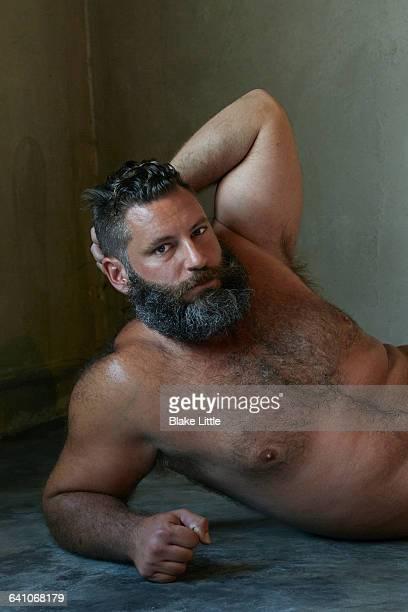 bearded shirtless man lying concrete floor - behaarte männer stock-fotos und bilder