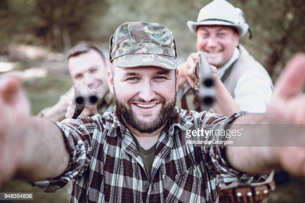 Bearded Smiling Hunter Making Selfie with Friend in the Forest