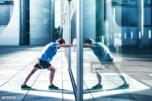 bearded sportsman pushing against glass