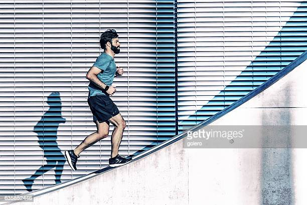 bearded sportsman running up on concrete wall in berlin