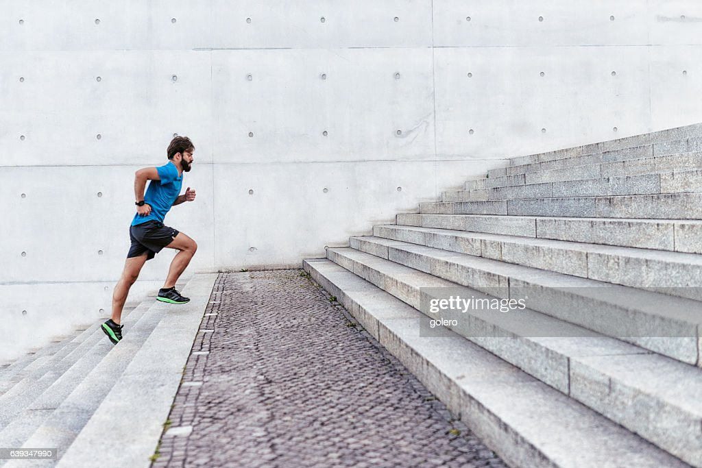 bearded sportsman running up outdoor stairway : Stock Photo