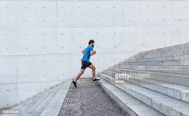 bearded sportsman running up stone stairway outdoors