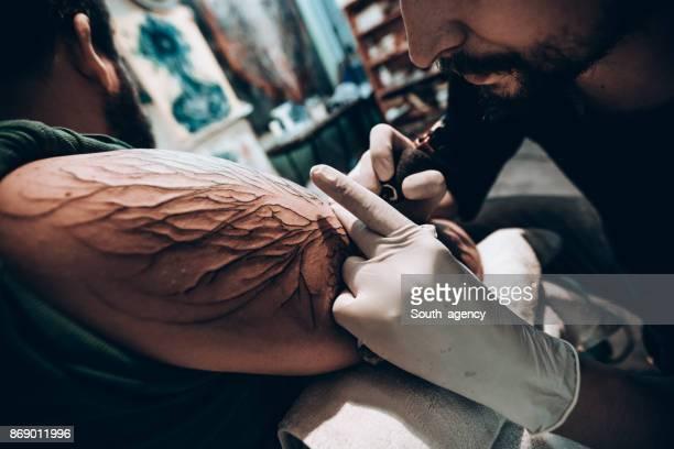 Bearded tattoo artist working