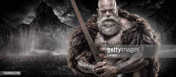 Bearded Tattooed Viking warrior king in front of warrior hoard and background