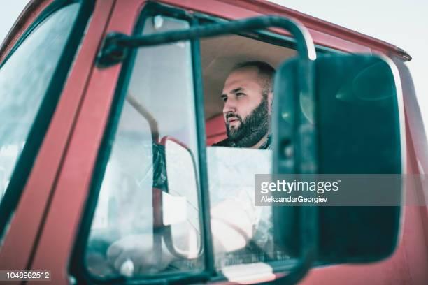conductor de camión barbudo con ventana abierta - camioneros fotografías e imágenes de stock