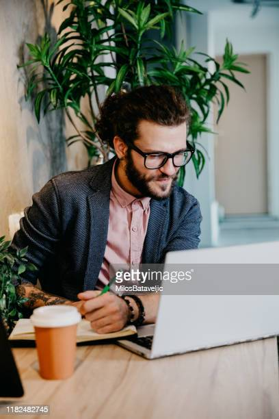 bearded young businessman working at modern office - smart casual stock pictures, royalty-free photos & images