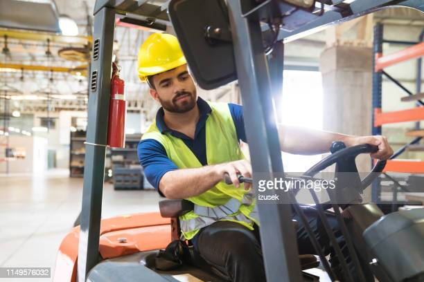 bearded young man driving forklift in factory - izusek stock pictures, royalty-free photos & images