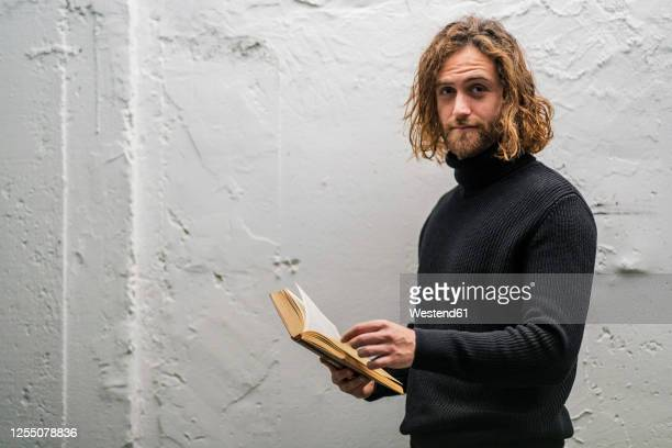 bearded young man holding book while standing against old wall at home - lang stock-fotos und bilder