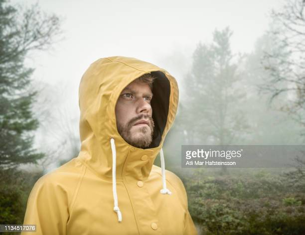 bearded young man in misty forest wearing hooded yellow raincoat looking away - raincoat stock pictures, royalty-free photos & images