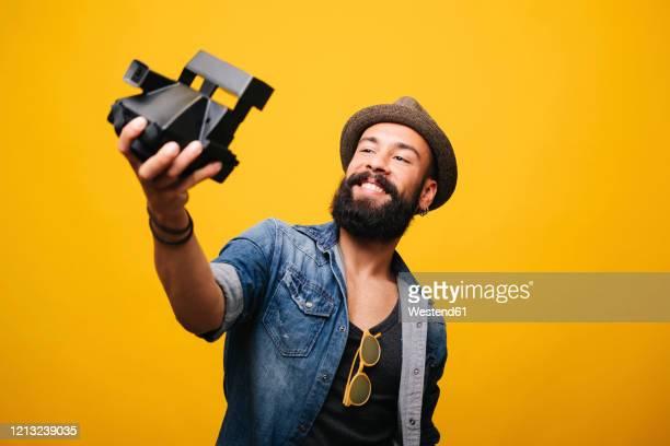 bearded young man in studio taking selfie with instant camera - 25 29 anos imagens e fotografias de stock