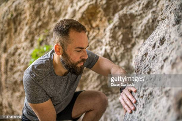 bearded young man is climbing mountain - dusan stankovic stock pictures, royalty-free photos & images