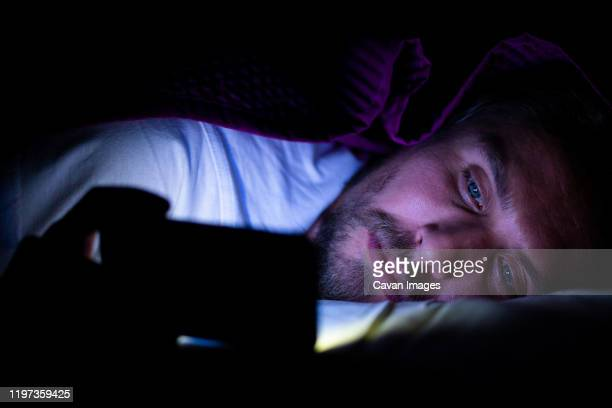 bearded young man is lying in bed under his blanket looking at phone - net sports equipment stock pictures, royalty-free photos & images