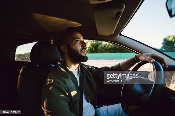 bearded young man looking at rear-view mirror while driving car - driver stock pictures, royalty-free photos & images