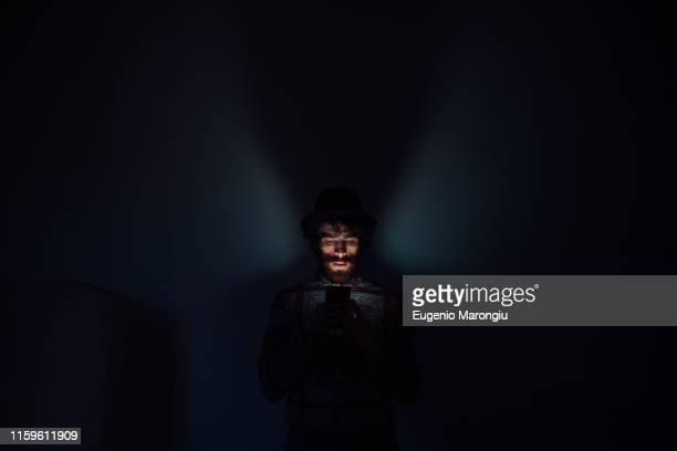 bearded young man using smartphone in dark room - darkroom stock pictures, royalty-free photos & images