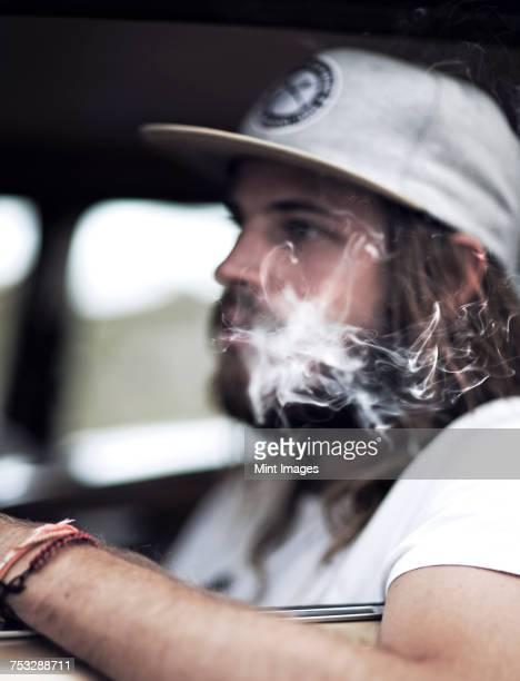 Bearded young man wearing baseball cap sitting in a car, smoking cigarette, cigarette smoke.