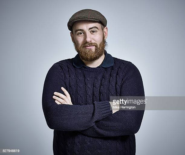 Bearded young man wearing cap and woolly jumper.