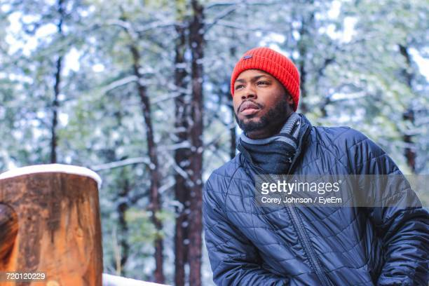 Bearded Young Man Wearing Warm Clothing In Forest During Winter