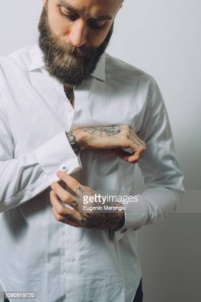 bearded young man wearing white shirt, doing up cuff links, tattoos on hands - 袖口 ストックフォトと画像