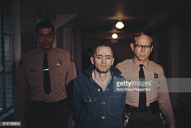 Beardless shavenheaded and sporting a swastika tattoo on his forehead Charles Manson convicted of the Sharon Tate and LaBianca murders is escorted by...