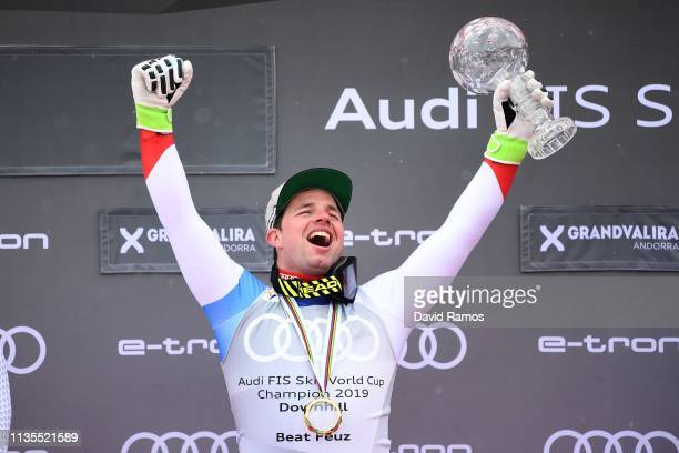 Beat Feuz of Switzerland celebrates winning the Audi FIS Alpine Ski World Cup with the trophy after the Men's Downhill on March 13 2019 in Andorra la...