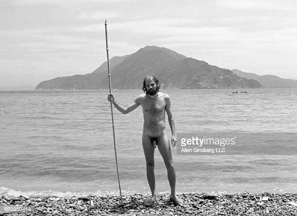 Beat poet Allen Ginsberg wearing only his birthday suit poses with a bamboo stick in his hand on the beach