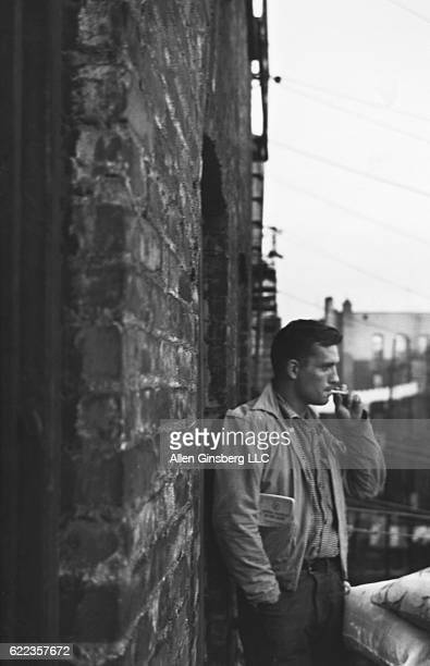 Beat poet Jack Kerouac smokes a cigarette on an apartment's fire escape in the Lower East Side