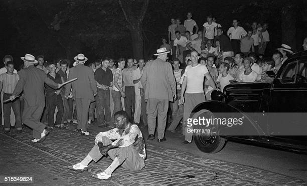 Beaten and bloody a negro sits in the middle of the street while police check members of the mob which attacked and stoned him during a racie riot...