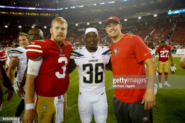 J Beathard and George Kittle of the San Francisco 49ers stands with former Iowa Hawkeye teammates Desmond King of the Los Angeles Chargers following...