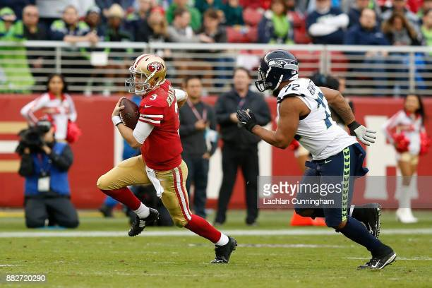 J Beathard of the San Francisco 49ers evades Michael Bennett of the Seattle Seahawks at Levi's Stadium on November 26 2017 in Santa Clara California