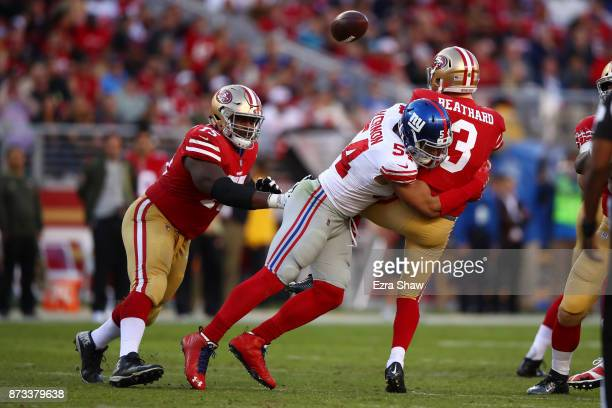 J Beathard of the San Francisco 49ers is hit against the San Francisco 49ershe throws by Olivier Vernon of the New York Giants during their NFL game...