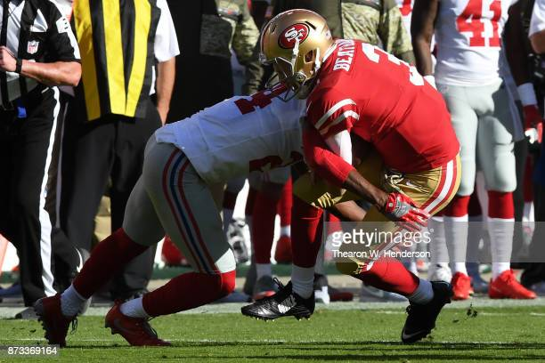 J Beathard of the San Francisco 49ers is hit by Eli Apple of the New York Giants during their NFL game at Levi's Stadium on November 12 2017 in Santa...
