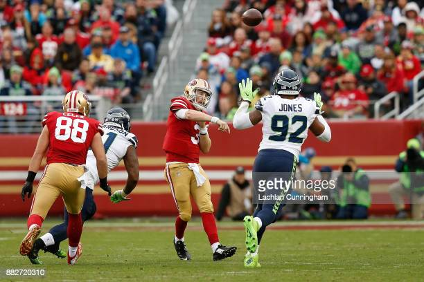 J Beathard of the San Francisco 49ers passes the ball past Nazair Jones of the Seattle Seahawks at Levi's Stadium on November 26 2017 in Santa Clara...