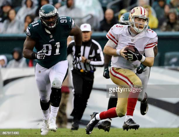 J Beathard of the San Francisco 49ers scrambles with the ball as Fletcher Cox of the Philadelphia Eagles defends in the second half on October 29...
