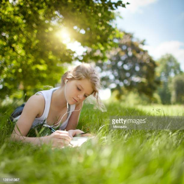 Beatiful Teenage Girl Studying in the Park