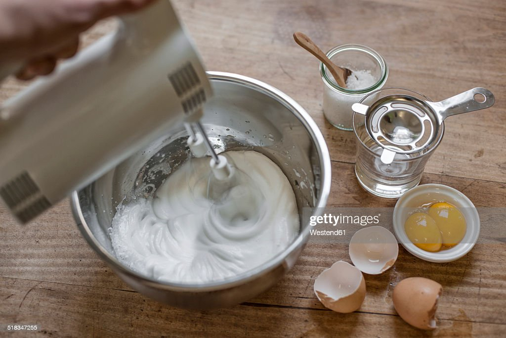 Beating egg white with electric whisk, elevated view : Stock Photo