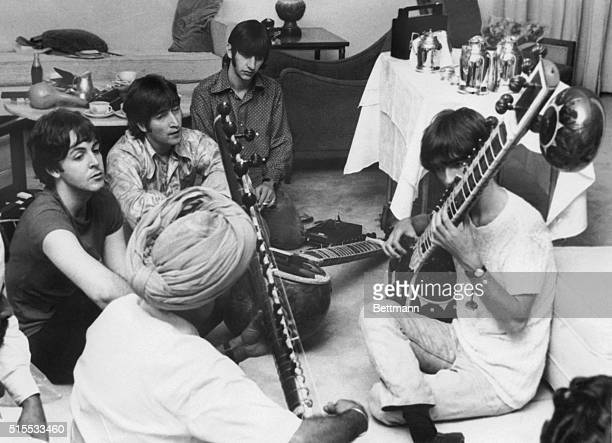 Beatle George Harrison receiving instruction in playing the sitar from a Sikh teacher as the other members of the Beatles look on in quiet...
