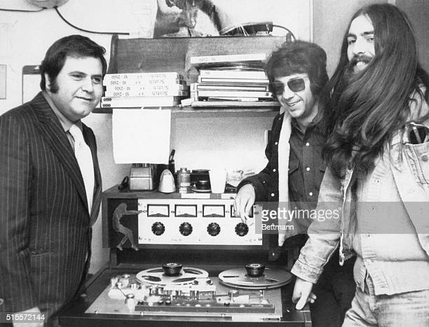 'Beatle' George Harrison sporting belowtheshoulderlength hair listens to master tape of his first solo album in recording studio here Cot 30 with...