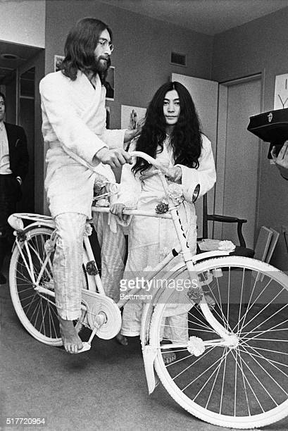 Beatle John Lennon tries out a bicycle he received as a gift while his new wife Yoko Ono stands by The couple are in pajamas and robes because they...