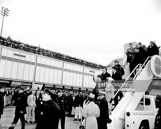 Beatles as they step triumphantly from plane at Kennedy Airport for the first time from London for a 10day tour