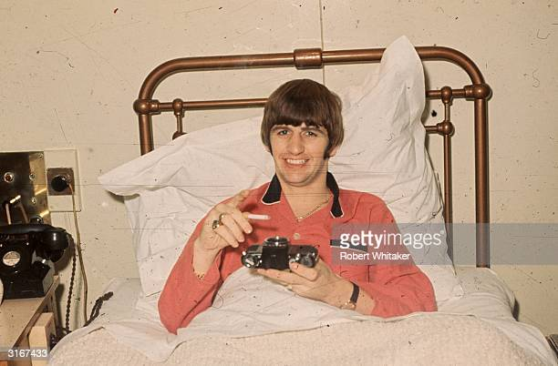 Beatles drummer Ringo Starr pictured in a hospital bed using a camera body as an ashtray Starr was having his tonsils removed at University College...