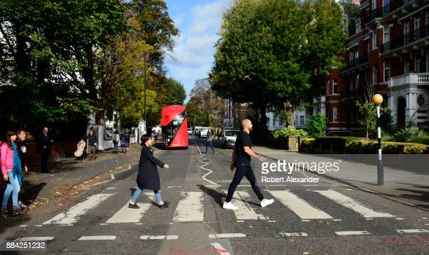 Beatles fans walk across Abby Road in London England recreating the famous 1969 Beatles 'Abby Road' album cover photograph showing the four musicians...