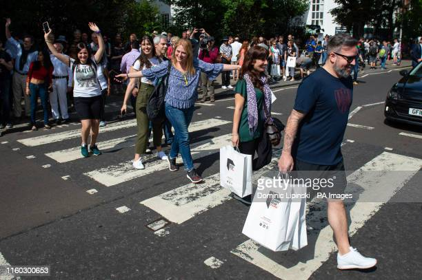 Beatles fans walk across the Abbey Road crossing in London as fans mark the 50th anniversary of the band doing it for their iconic album cover on 8...