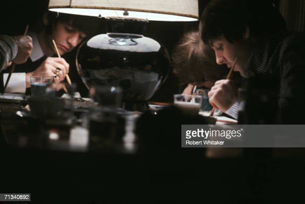 Beatles George Harrison Ringo Starr John Lennon and Paul McCartney busy completing their only known collaborative artwork 'Images of a Woman' at the...
