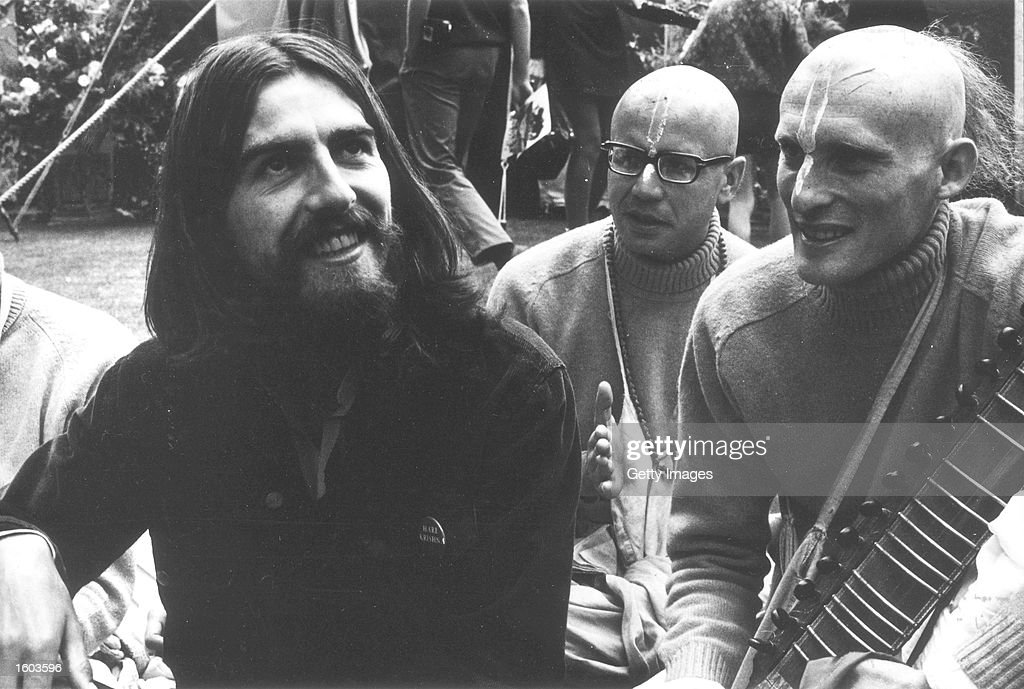Beatles Guitarist And Singer George Harrison Sits With Shaven Headed Members Of A Hindu Sect