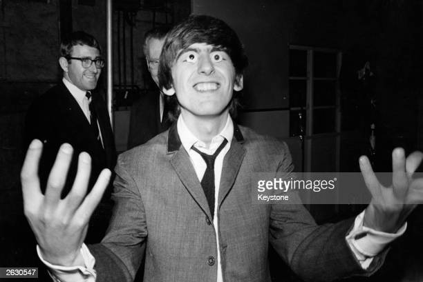 Beatles guitarist George Harrison tries out a pair of false eyes made by Madame Tussaud's waxwork museum where models of The Beatles are being created