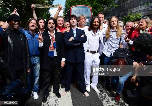Beatles impersonators pose after recreating the iconic 'Abbey Road' photograph made 50 years ago today on August 8 2019 in London England 50 years...