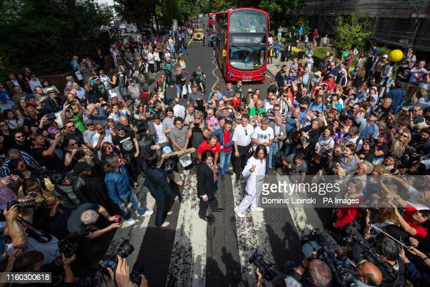 Beatles lookalike band 'Fab Four' joins Beatles fans as they walk across the Abbey Road crossing in London on the 50th anniversary of the band doing...
